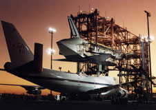 Evening light begins to fade at NASAs Dryden Flight Research Center as technicians begin the task of mounting Space Shuttle Atlantis atop one of NASAs 747 Shuttle Carrier Aircraft for the ferry flight back to the Kennedy Space Center, Fla., following its STS-44 flight in late 1991.