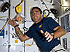 Astronaut stands with items floating in microgravity and attached to the wall with Velcro