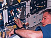 Richard Searfoss attaches space food to Velcro on the wall of the space shuttle