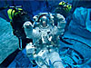 Astronaut wears spacesuit underwater with two divers behind her