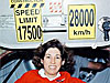 Ellen Ochoa poses with signs that show the speed of the station