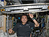 Man on the space station holds treadmill above his head with one finger