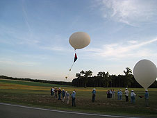 People stand in a field launching white scientific balloons