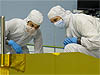 Two men in clean room suits look at a space telescope mirror