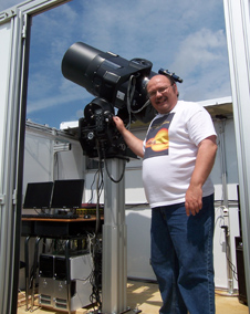 Bill Cook stands beside a large telescope