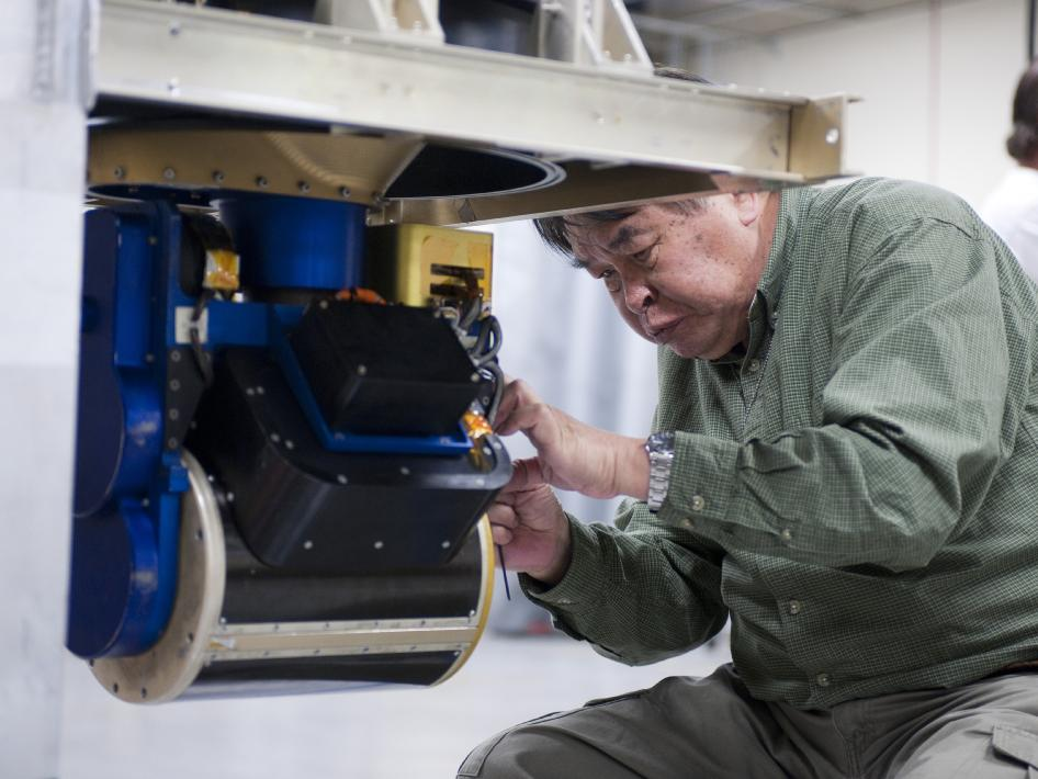 A Goddard engineer adjusts the CoSMIR scan head prior to installation in NASA's DC-8 flying science laboratory.