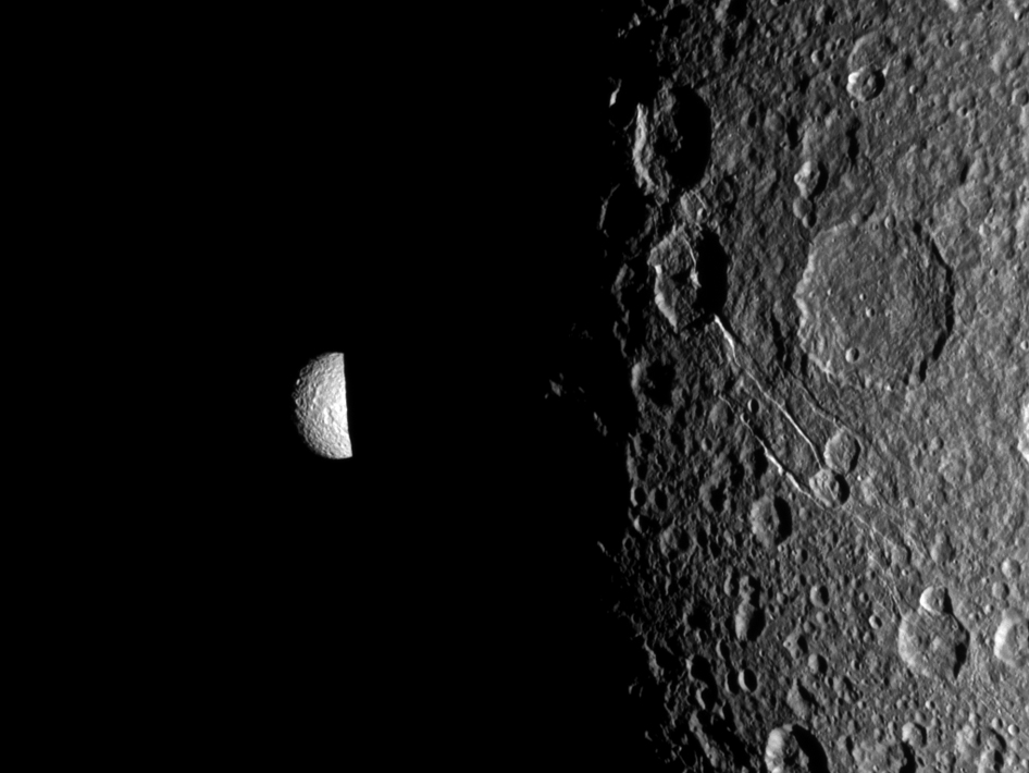 Saturn's moon Mimas peeks out from behind the night side of the larger moon Dione