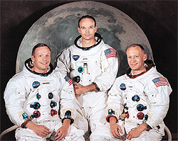 The Apollo 11 astronauts in their spacesuits sitting in front of a large picture of the Moon