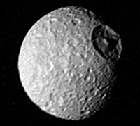 Black and White image of the heavily-crater surface of Saturn's moon, Mimas, including a massive 62-mile wide crater that dominates the moon's surface