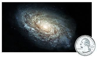 This picture shows a galaxy seen from above at an angle.  The Galaxy is a swirling white and light blue spiral of gas and dust on a black background.  In the corner of the image is a picture of the face side of a quarter coin.