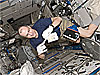 Astronaut Don Pettit prepares a science experiment as he floats on the space station