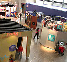 Image shows a view from above of the exhibit floor, visitors walk around the tiled floor between various components of the exhibit.
