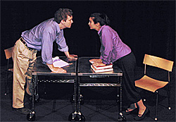 Image shows a theatre stage, black floor and background.  Two desks are set to face each other and two students, male and female, are standing, facing one another, and leaning on their hands on the desks.  Chairs are behind each of the students.