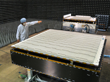 A JAXA scientist standing next to the Dual-frequency Precipitation Radar (DPR) instrument for the GPM Core Observatory satellite. The Japanese-built radar is a new instrument designed to take 3-D measurements of raindrops and snowflakes.