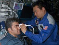 Using the Advanced Diagnostic Ultrasound in Microgravity (ADUM) protocols, ISS Expedition Commander Leroy Chiao performs an ultrasound examination of the eye on Flight Engineer Salizhan Sharipov. (NASA)