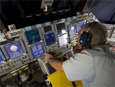 A technician monitors data displayed in Atlantis' glass cockpit during preparations to power down