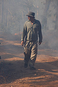 Chris Justice walks through smoke on a dirt road