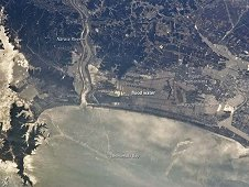 Oblique image of the Japanese coastline north and east of Sendai following inundation by a tsunami. (NASA)