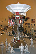 Engineers in protective gear surround the Cassini spacecraft in a cleanroom at Kennedy Space Center.