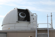 The telescope on NASA Goddard's Next Generation Satellite Laser Ranging system peeks through the open dome.