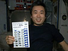 Astronaut Wakata displays a bisphosphonate distribution card while aboard the International Space Station. (NASA)