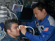 Using the ADUM protocols, ISS Expedition Commander Leroy Chiao performs an ultrasound examination of the eye on Flight Engineer Salizhan Sharipov. (NASA)