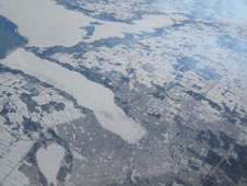 The snow-covered city of Barrie, Ontario, Canada, surrounds ice-bound Lake Simcoe in this view from NASA's DC-8 airborne science laboratory during a flight Feb. 20.
