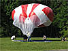 A red and white weather balloon being deflated by people in a meadow