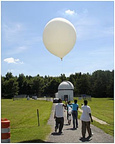 Students walk along a concrete path in the middle of a field with a large weather balloon
