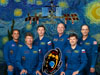 Six astronauts in blue flight suits in front of artwork showing the space station