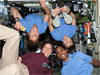 Four female astronauts float inside the International Space Station