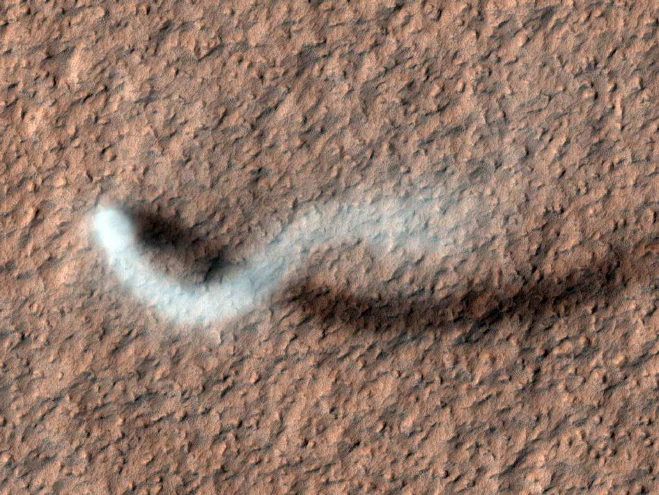 A towering dust devil, casts a serpentine shadow over the Martian surface