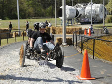 Two students pedal a moonbuggy over a mound of gravel
