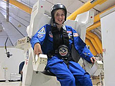A girl in a blue Space Camp flight suit sitting in a simulator