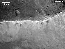 The interplay of bright and dark material at the rim of Marcia crater on Vesta is visible in this image mosaic taken by NASA's Dawn spacecraft.
