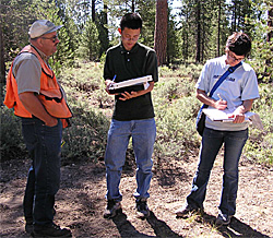 Photograph of Michael Jin and Catherine Huybrechts taking notes while speaking with the U.S. Forest Service's Karl Greulich
