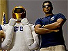 A picture of Robonaut standing next to a man in a blue shirt and tan pants