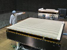 A JAXA scientist standing next to the completed DPR