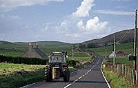 Photograph of a tractor driving down a road