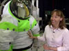 Amy Ross stands beside a spacesuit
