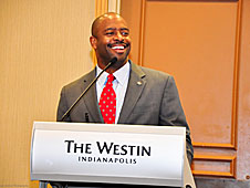Leland Melvin stands at a podium