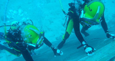 Two NEEMO crew members perform simulated asteroid activities.