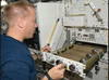 Astronaut Tim Kopra working at an experiment rack