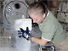 Astronaut Shannon Walker wears thick gloves as she lifts a very cold experiment