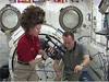 Two astronauts measure an experiment