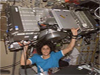 Astronaut Sunita Williams holds a piece of equipment over her head