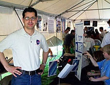 Man standing near science fair exhibits under a tent