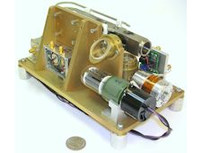 A laboratory representation of the Deep Space Atomic Clock, with a quarter alongside the unit for size comparison.