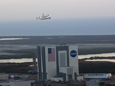 Discovery and the SCA fly past the Vehicle Assembly Building