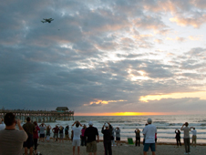 Observers near the Cocoa Beach Pier watch as Discovery flies over area beaches